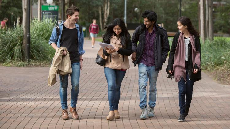 International students walking on path near duckpond lawn at Wollongong campus