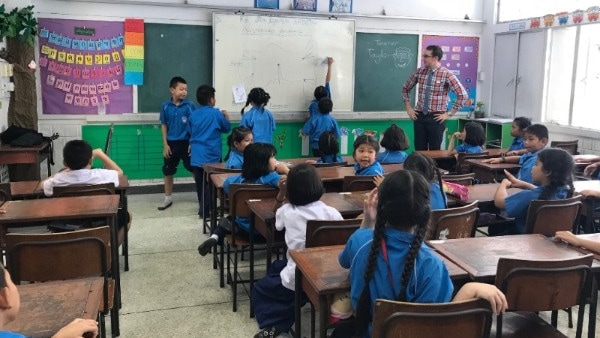 Taylor Weule in Thai primary school classroom with students drawing on board and sitting at desks