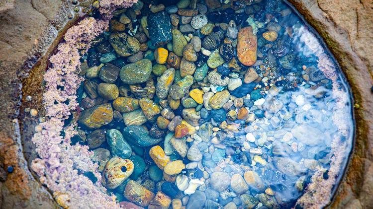 Birdseye view of rock puddles filled with stones and water