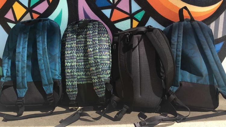 4 school backpacks lined up against wall