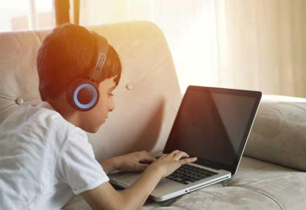 child with headphones lays on couch with lap top