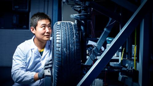 Shuai Shuai Sun MR technology researchers looks at the underboady of a vehicle
