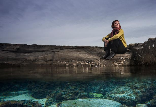 UOW researcher Leah Gibbs sits on rocks near water