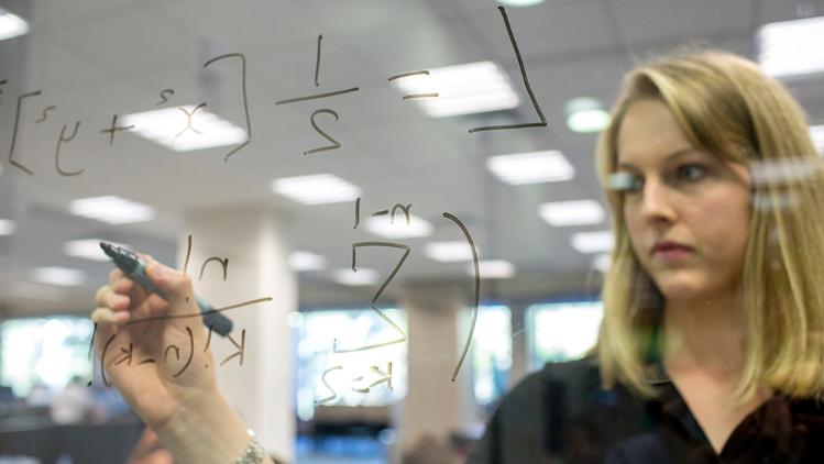 Female student studying/writing algebra on a translucent white board