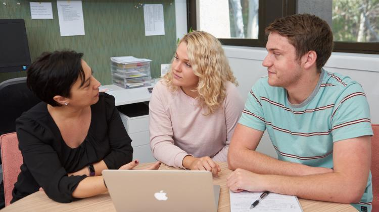 Two students consult with a UOW staff member