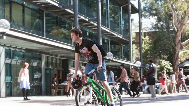 Student riding bike on Wollongong campus outside Library