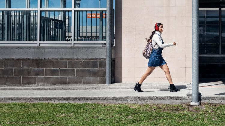 A student walking with purpose in front of North Wollongong train station
