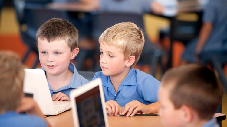 Two primary school boys play on tablets in a classroom