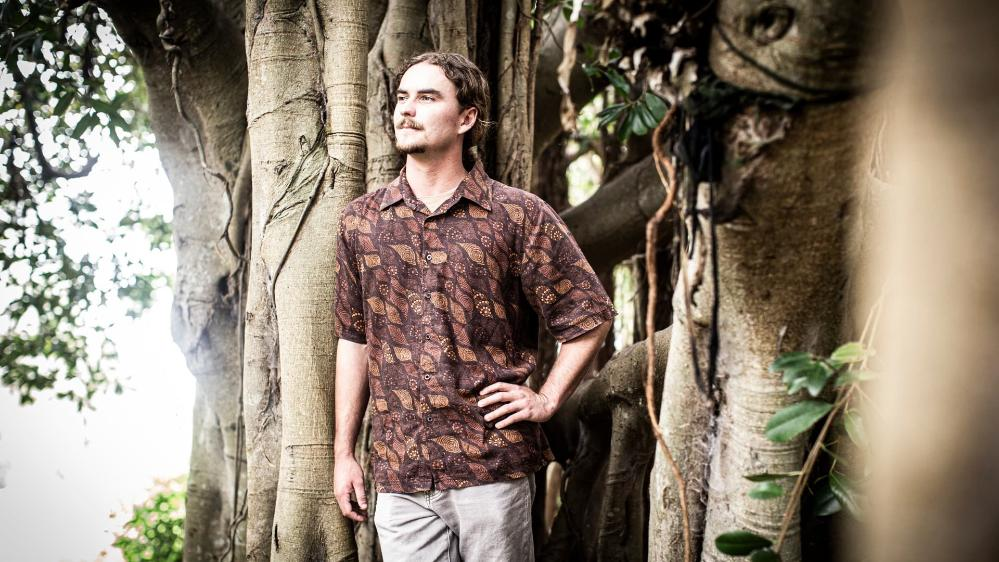 UOW student Charlie Gluskie stands next to a tree, surrounded by bush. Photo: Paul Jones