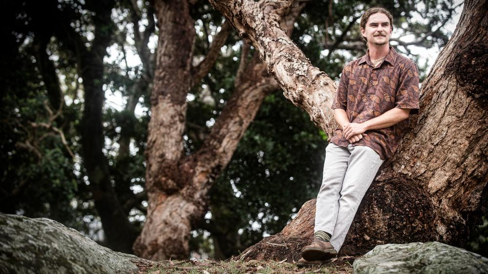 UOW student Charlie Gluskie sits in a tree, surrounded by bush. Photo: Paul Jones
