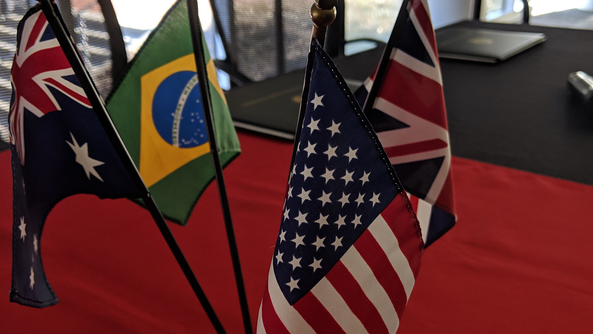 Image from 2019 UGPN conference of Australian, Brazilian, UK and USA flags on a deskflags