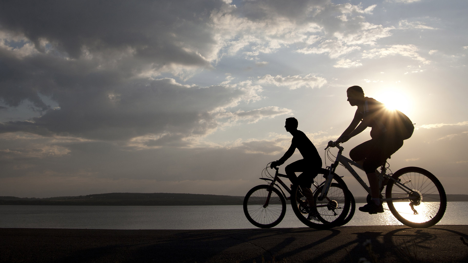Bicycle riders at sunset. Shutterstock image